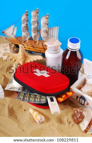 first aid box with medicines and thermometer  on the beach as healthy summer holiday concept - stock photo