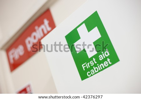 First aid cabinet and fire point label - stock photo