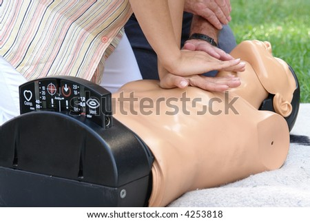 First aid instructor showing resuscitation technique on dummy - stock photo