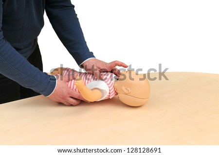 first aid instructor using infant dummy demonstrating how to rescue a baby - stock photo