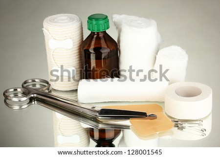 First aid kit for bandaging on grey background - stock photo