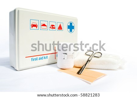First aid kit with bandages and scissors on white background - stock photo