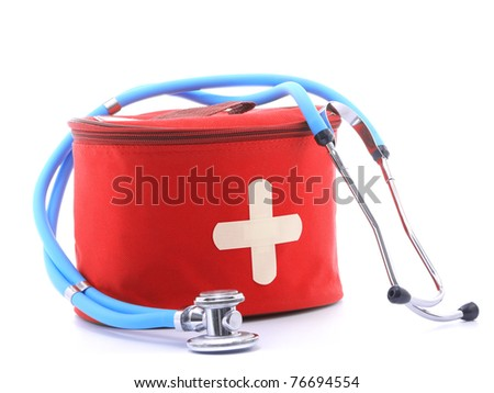 First-aid kit with white cross as two crossed band-aid slips and blue stethoscope over white background - stock photo