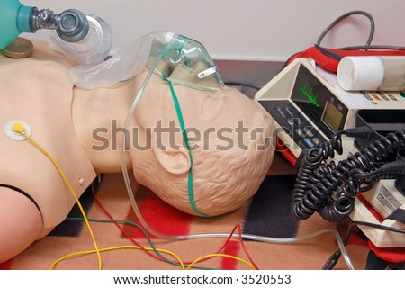 First-aid training dummy with respiratory mask and sensors connected to electrocardiograph unit - stock photo
