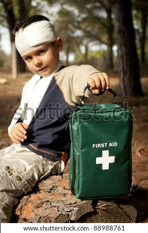 First Aid treatment given to a young boy in the forest, showing an arm sling and a head injury. - stock photo