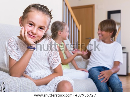 First amorousness:  spanish girl and couple of kids apart indoors - stock photo