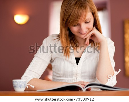 First cappuccino - Beautiful young caucasian girl drinking coffee in a bar in early morning - stock photo