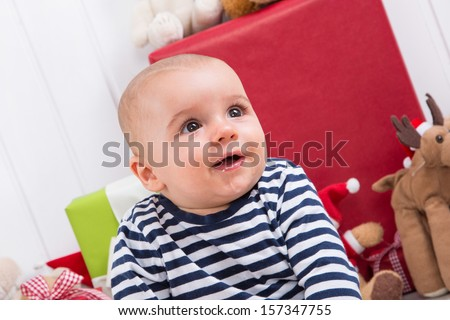 First Christmas: baby amongst presents - children eyes - stock photo