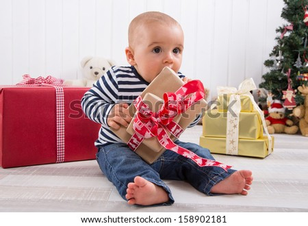 First Christmas: barefoot baby unwrapping a red present - stock photo