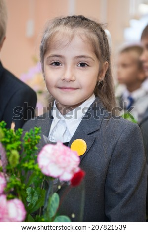 First class student in uniform looking at camera - stock photo