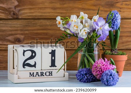 First day of spring flowers and calendar - stock photo