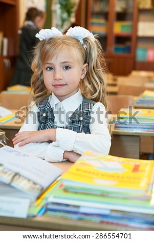 First-form cute schoolgirl sitting at school desk in classroom, looking at camera - stock photo