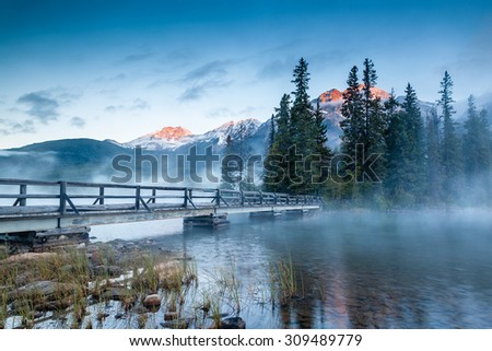 First glimpse of a golden sunrise on a misty and foggy morning at Pyramid Lake in Jasper National Park, Alberta, Canada. The wooden bridge leads to Pyramid Island on the lake. - stock photo