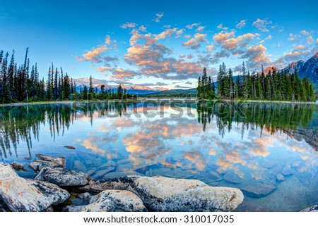 First glimpse of golden sunrise at Pyramid Lake in Jasper National Park, Alberta, Canada. The clouds reflect off the calm waters. - stock photo