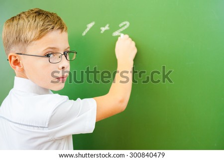 First grade schoolboy wrote on blackboard with chalk - arithmetic digits One Plus Two, and looking at the camera. Boy dressed in a white shirt and wearing glasses. Concept of knowledge day - stock photo