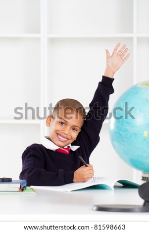 first grade student raising his hands in classroom - stock photo