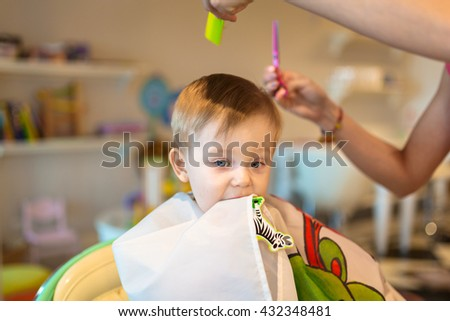 First haircut of one years old toddler - stock photo