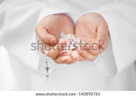 First Holy Communion concept - close up on rosary on child's hands - stock photo