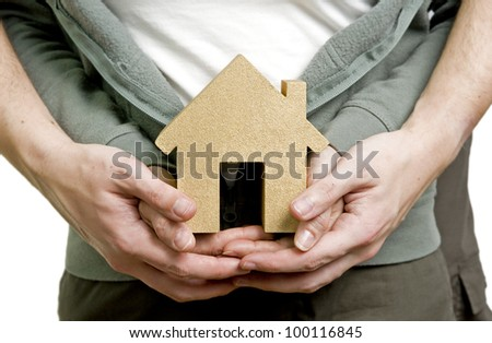 first house, man and woman couple holding golden model house - stock photo