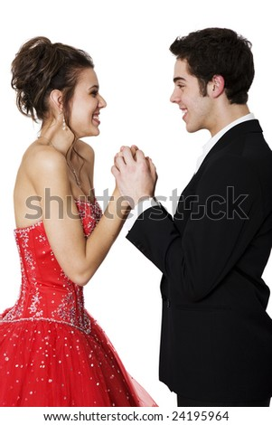 First love.  Boy & girl, in formal attire, holding hands & smiling at each other. - stock photo