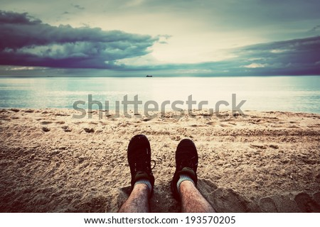 First person perspective of man legs on the autumn beach. Vintage, retro style - stock photo