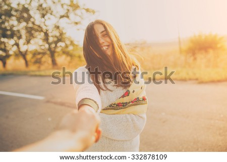 First person portrait of a smiling girl holding hand on sunset. Adorable young woman on sunny day