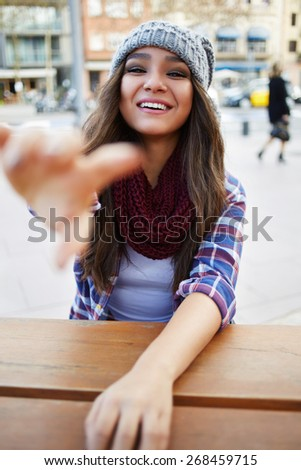 First person portrait of a young brunette woman smiling brightly and engagingly at you, gorgeous young woman laughing at the camera, lunch in coffee shop during honeymoon vacations - stock photo