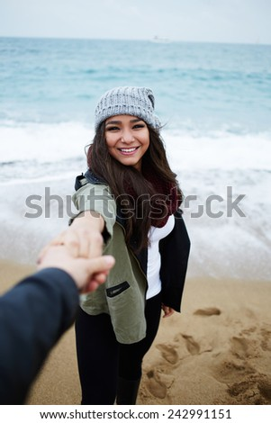 First-person portrait of charming girlfriend holding boyfriend hand, young couple in love at romantic walk on the beach - stock photo