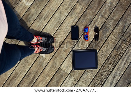 First person top view shot with blank screen tablet, smart phone and two of sunglasses, female legs standing on wooden floor with everyday objects lying, modern business person or freelancer set kit - stock photo