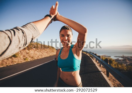 First person view of a man and woman high fiving. Happy young woman giving high five to man after outdoor training. Couple of runner on country road looking happy. - stock photo