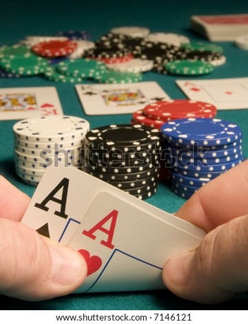 First person view of pocket aces in a game of Texas Hold-em with a full house showing on the board - stock photo