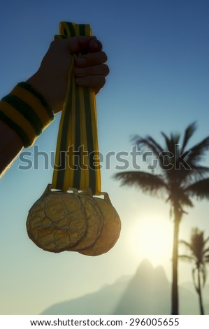 First place athlete holding gold medals in front of the sunset on Ipanema Beach Rio de Janeiro Brazil  - stock photo