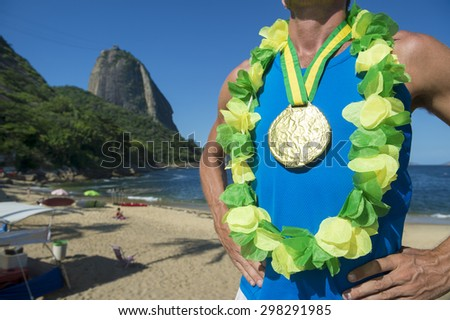 First place athlete wearing gold medal and Brazil colors lei standing outdoors in front of Sugarloaf Mountain Rio de Janeiro - stock photo