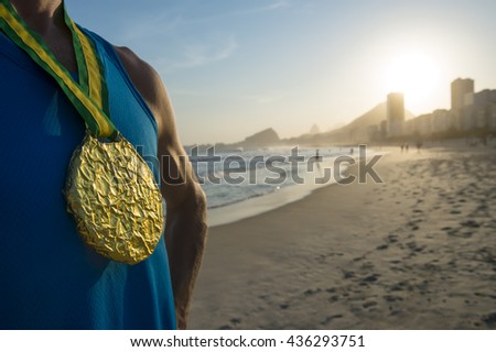 First place athlete wearing gold medal in front of the sunset on Ipanema Beach, Rio de Janeiro, Brazil