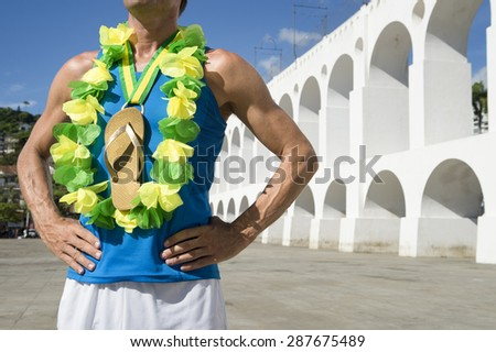 First place Brazilian athlete standing with flip flop gold medal at the Arcos da Lapa Arches in Rio de Janeiro Brazil - stock photo