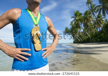 First place Brazilian athlete standing with flip flop gold medal on empty beach - stock photo