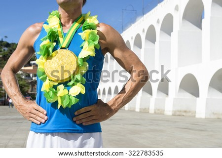 First place Brazilian athlete standing with gold medal and Brazil colors lei at the Arcos da Lapa Arches in Rio de Janeiro - stock photo