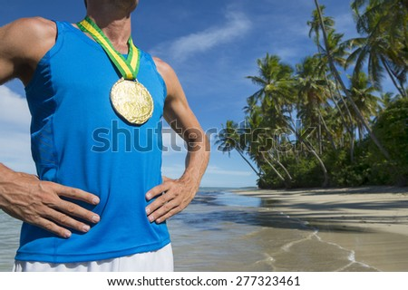 First place Brazilian athlete standing with gold medal on empty beach - stock photo