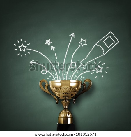 First place championship trophy or cup in front of blackboard with champagne and fireworks concept for winning and success - stock photo