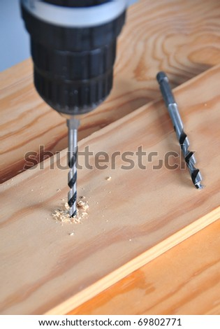 first plane of drill tool carrying out a hole has more than enough wooden list - stock photo