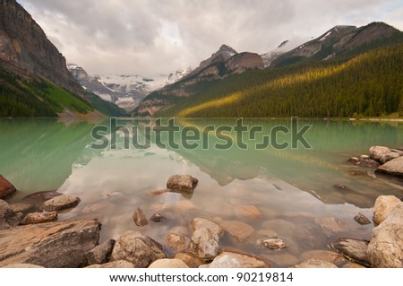 First rays of golden sunlight on the mountains at Lake Louise with peaceful reflections.