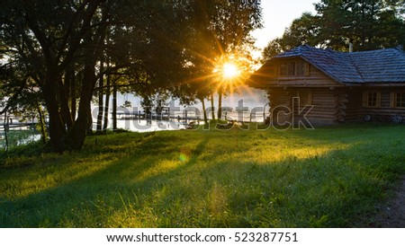 First rays of the sun above lake and forest house, Belarus, Summer
