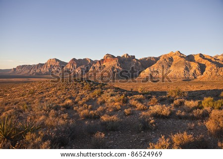 First rays of warm sunrise light in Nevada's Red Rock National Conservation Area. - stock photo