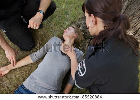 First responder medical team attending to sick woman - stock photo
