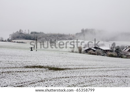 first snow in countryside, man walking with two dogs - stock photo