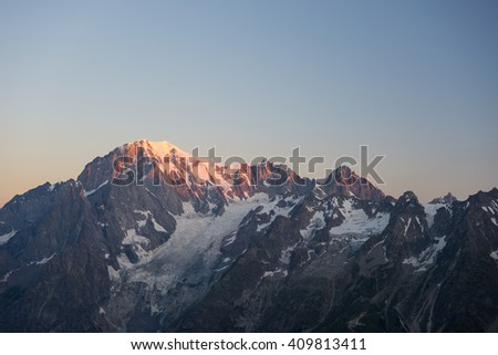 First soft light at sunrise over Monte Bianco or Mont Blanc summit (4810 m) and his melting glaciers. View from 3000 m in Valle d'Aosta. Summer adventures on the italian french Alps. - stock photo