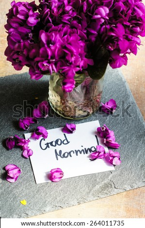First spring flowers on the table with good morning note