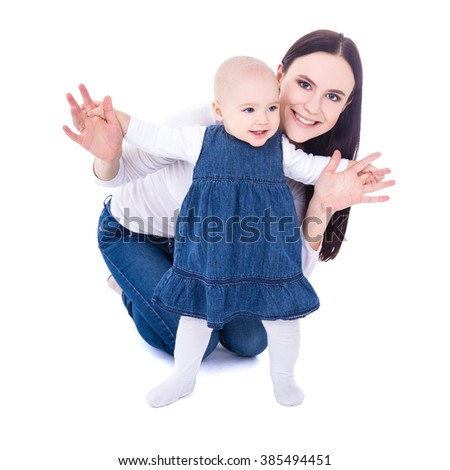 first step concept - young mother with baby girl learning to walk isolated on white background - stock photo
