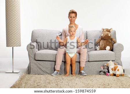first step, Mother and baby daughter playing in living room - stock photo