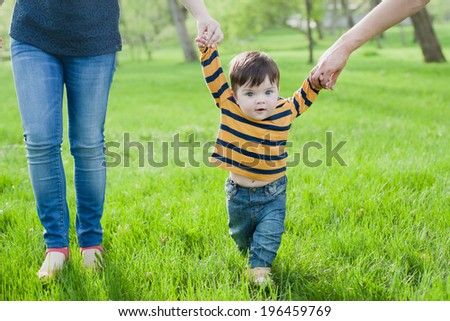 First steps. Baby learning to walk, with help of mothers and fathers hands. - stock photo